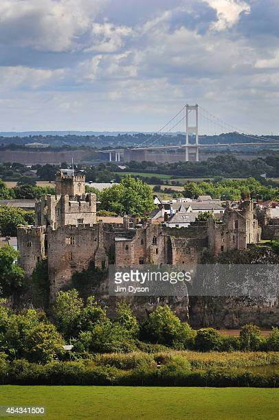A view looking across the River Wye to the clifftop ruins of Chepstow Castle as the Severn suspension Bridge to England rises in the background on...