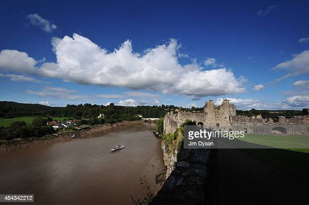 A view looking across the River Wye to the clifftop ruins of Chepstow Castle with the Old Wye Bridge to Gloucestershire England in the background...