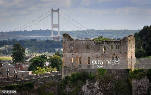 A view looking across the River Wye to the clifftop ruins of the great tower at Chepstow Castle as the Severn suspension Bridge to England rises in...