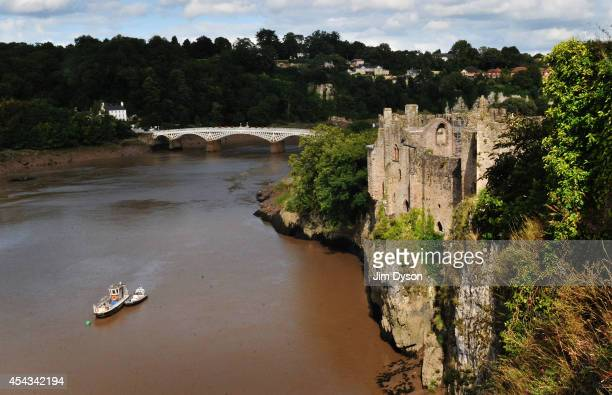 A view looking across the River Wye towards the clifftop ruins of Chepstow Castle with the Old Wye Bridge to Gloucestershire England in the...