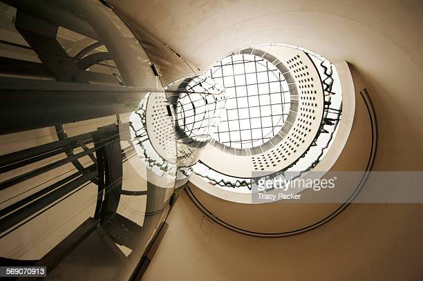 A view looking directly up past a reflective glass elevator shaft to the top floor and the circular skylight in the roof space of the Post Modern...