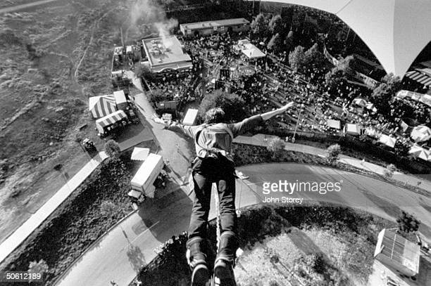 View looking down on a bungee jumper as he takes off from platform high above the carnival tents crowd at the Lollapalooza '92 traveling rock fest...