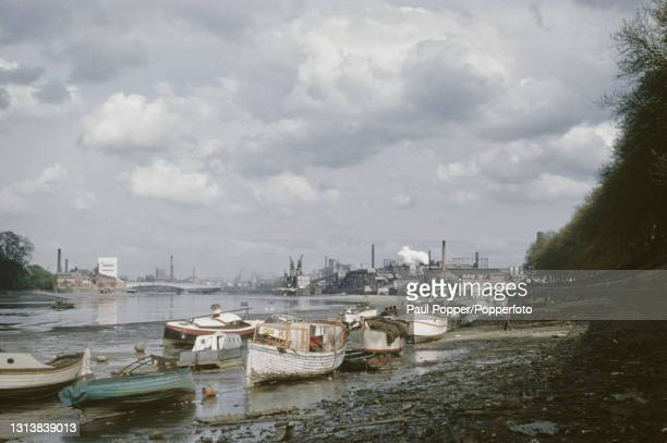 View looking east from Putney of boats moored at low tide on the banks of the River Thames at Wandsworth in London circa 1960. Industrial buildings...