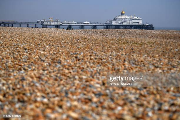 A view looking east towards the pier across a deserted beach in Eastbourne on the south coast of England on April 12 as life in Britain continues...