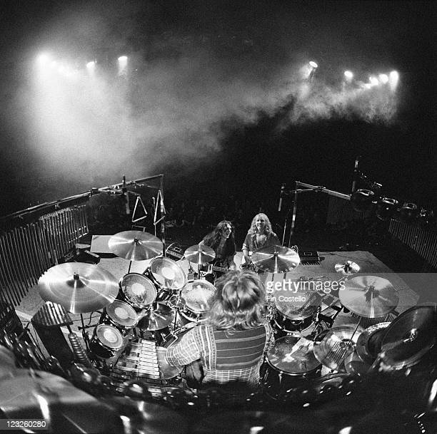 View looking from the back of the stage looking out over drummer Neil Peart sitting at his drumkit with guitarist Alex Lifeson and bassist Geddy Lee...