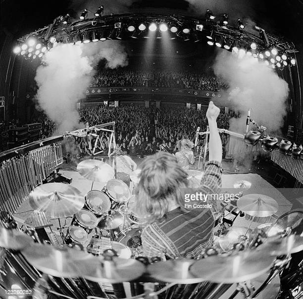 View looking from the back of the stage looking out over drummer Neil Peart sitting at his drumkit with an arm raised aloft guitarist Alex Lifeson...