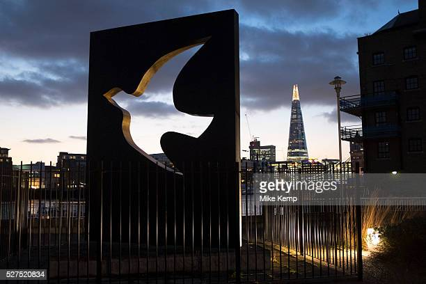 View looking past the Peace Dove Sculpture Hermitage Wharf Riverside Memorial Garden to the skyline of Tower Bridge and The Shard in London UK One of...