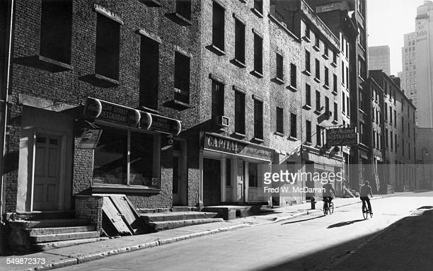View looking south as a pair of bicyclists ride along Cliff Street in Lower Manhattan New York New York October 6 1963 Visible businesses include the...