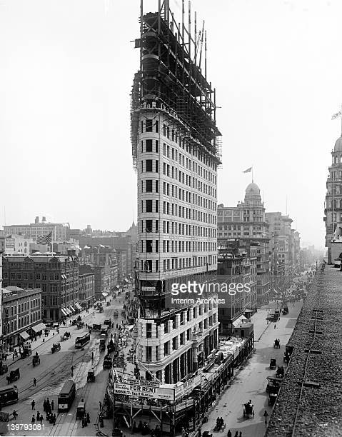View looking south of the Flatiron Building or the Fuller Building under construction in New York City 1902 The busy pedestrian and vehicular traffic...