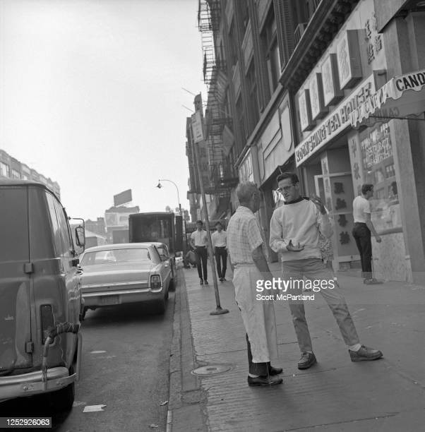 View looking southeast along Canal Street of two men as they talk on the sidewalk in the Chinatown neighborhood New York New York August 1968 One of...