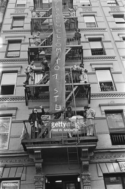 View looking up as a number of unidentified people as they stand on a building's fire escape on either side of a banner that stretches at least five...