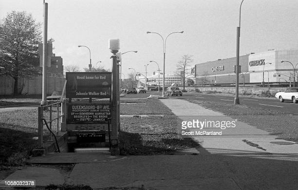 View looking west on Queens Boulevard past the entrance to a station on the Independent Subway System Queens New York New York September 1980 Visible...