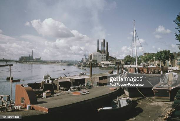 View looking westwards and upstream from Battersea Bridge of boats moored at low tide on the north bank of the River Thames at Chelsea Embankment in...