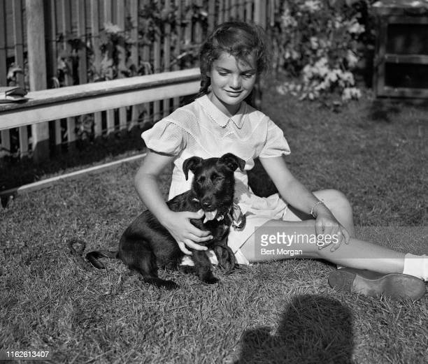 View of 10-year-old Jacqueline Bouvier as she seats on the grass with her dog, Tammy, during a dog show in East Hampton Fair, Long Island, New York....