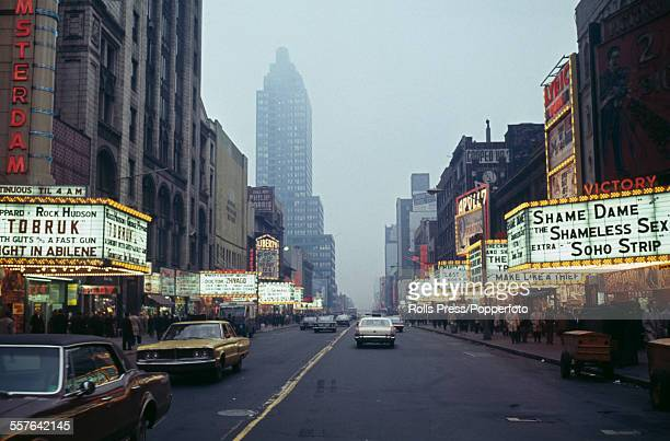 View of 42nd street at Times Square with marquees above cinemas advertising both Hollywood and pornographic films on presentation in New York in...