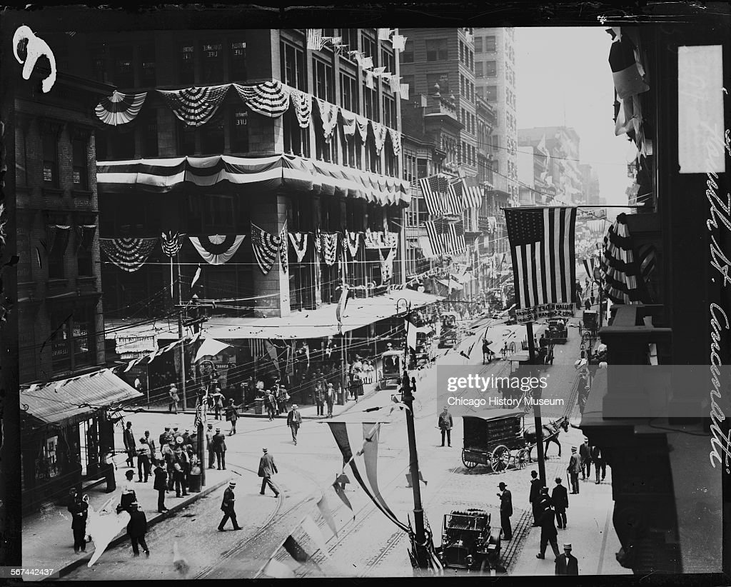 View of 4th Street, with buildings decorated with banners, swags, and United States flags, Cincinnati, Ohio, 1908. Some of the flags read: Taft for president. Pedestrians and horse drawn wagons are moving along the street. From the Chicago Daily News collection.
