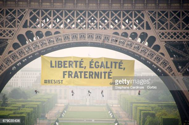View of a banner reading 'liberty equality fraternity' hung by Greenpeace activists on the Eiffel Tower to protest against the farright Front...