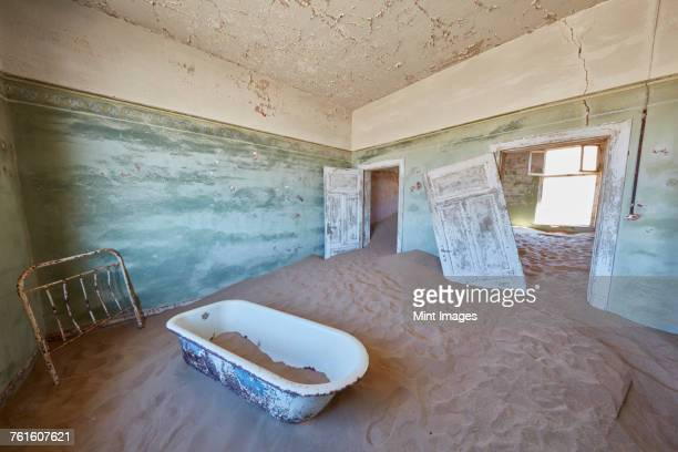 A view of a bathroom in a derelict building full of sand.