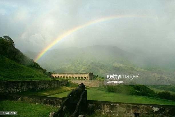 view of a beautiful rainbow arched amidst vast and lush meadows, st. kitts, leeward islands, caribbean - st. kitts stock photos and pictures