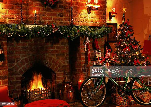 view of a bike parked beside a Christmas tree in a decorated living room with a lit fireplace