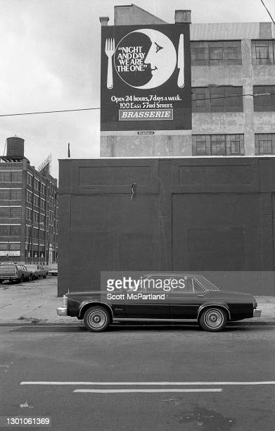 View of a billboard advertising Brasserie Restaurant on the side of a warehouse on an unidentified street in Long Island City, Queens, New York, New...