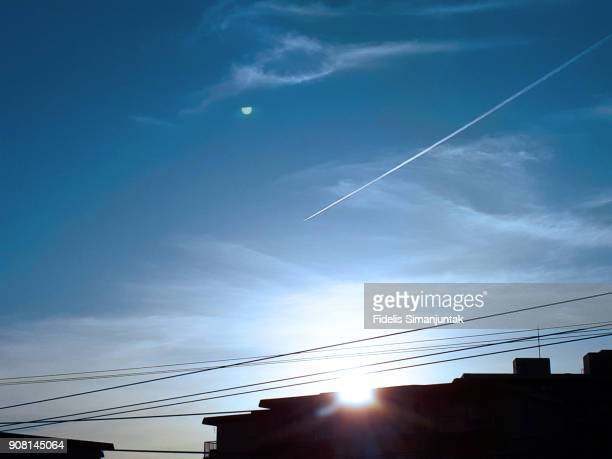 View of a blue clean sky with white vapor trails of planes and sunbeam