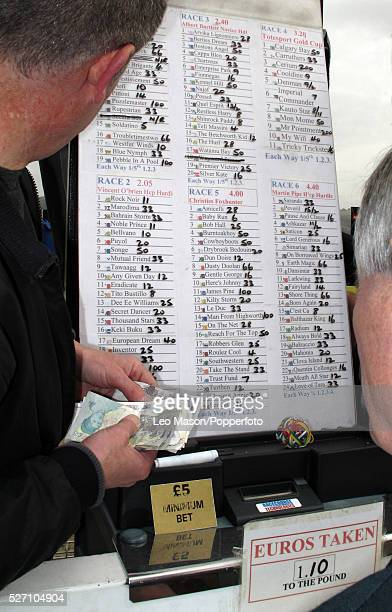 View of a bookmaker taking bets from punters and race goers on Gold Cup Day during the Cheltenham National Hunt Festival at Cheltenham Racecourse...