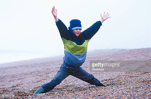 view of a boy (8-10) standing on the beach with feet apart and arms raised