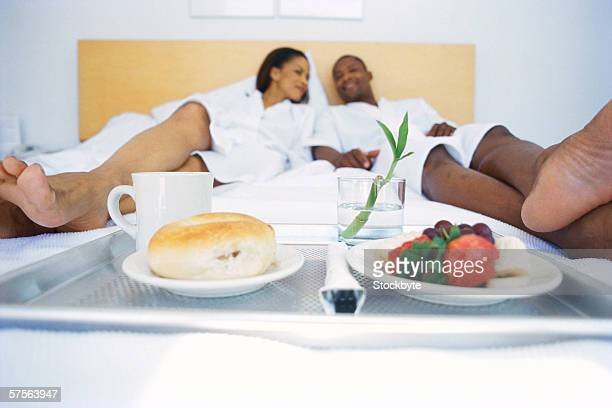 view of a breakfast tray lying on the bed at the feet of a young couple - black men feet stock photos and pictures