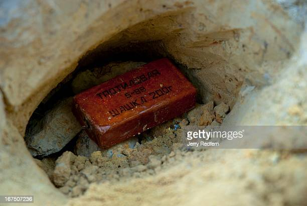 BAN PHONPHANPEK KHAMMOUANE LAOS View of a brick of Russian TNT sitting atop a pair of BLU24 cluster bomblets found in a hole in a garbage pit in the...