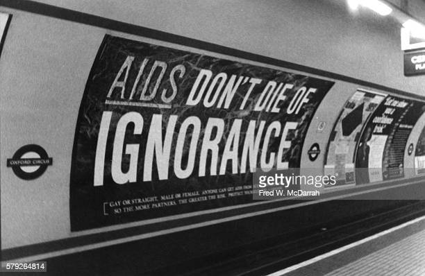 View of a British AIDS awareness poster in Oxford Circus tube or subway station London England March 8 1987 The text reads in part 'AIDS Don't Die of...