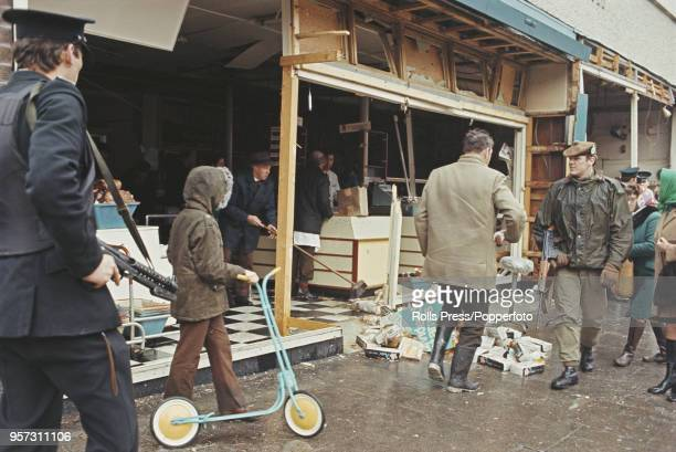 View of a British Army soldier and member of the Royal Ulster Constabulary standing guard outside a bomb damaged shop as staff clear up following the...