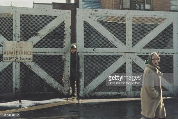 View of a British Army soldier standing on guard at a large peace line gate beside a military post that marks the dividing line between the...