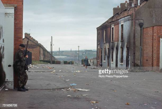 View of a British Army soldier watching a woman returning home with shopping bags as she walks past burnt out houses in the predominantly Catholic...