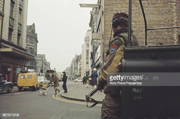 View of a British Army soldier wearing a maroon beret standing guard as residents visit shops and businesses in the centre of Belfast Northern...
