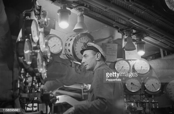 View of a British naval engineer and stoker operating controls in the boiler room of a Royal Navy Halcyonclass minesweeper during an operational...