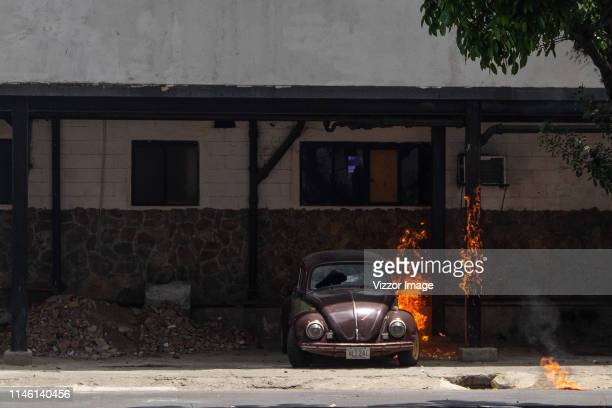 View of a broken car and a burning house around Altamira disttribuitor on April 30 2019 in Caracas Venezuela Through a live broadcast via social...
