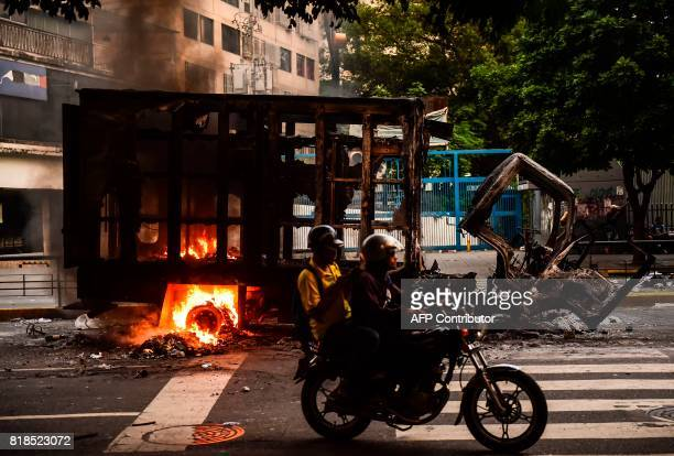 TOPSHOT View of a burned truck during clashes between opposition activists and the police in Caracas on July 18 2017 Venezuela's government on...
