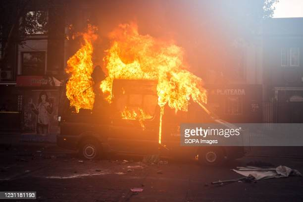 View of a burning police vehicle during the demonstration. Several protesters took to the streets to protest against President Sebastian Pinera's...