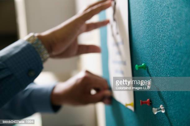 view of a businessman's hand pinning up paper on a notice board - bulletin board stock pictures, royalty-free photos & images