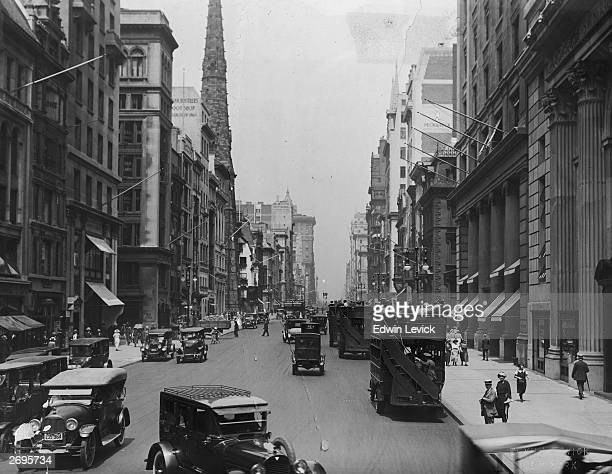 View of a busy street with automobiles and pedestrians possibly Fifth Avenue New York City