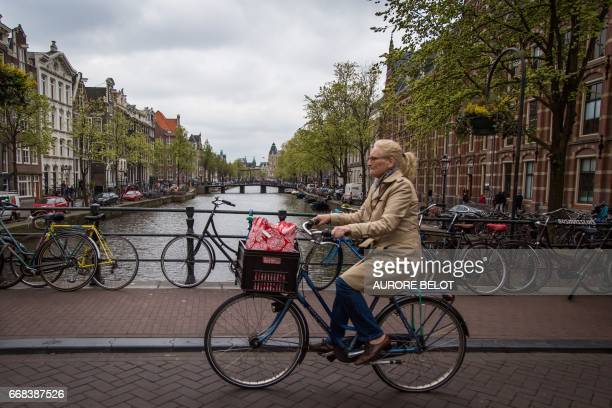 View of a canal in Amsterdam with a woman on a bicycle on April 12 2017 / AFP PHOTO / Aurore Belot
