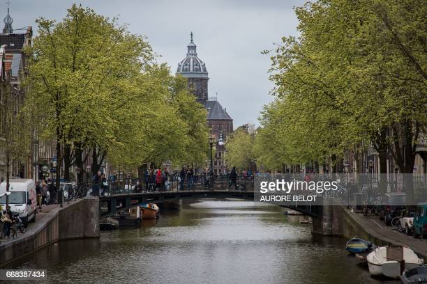 View of a canal with a Church in the background in Amsterdam on April 12 2017 / AFP PHOTO / Aurore Belot