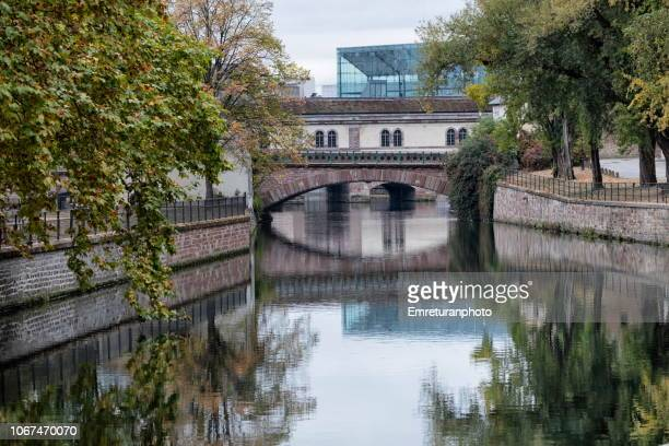 View of a canal with bridge and trees in Petite France.