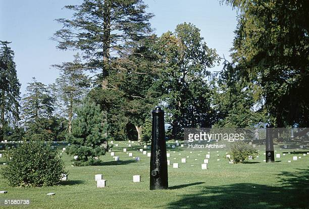 A view of a cannon upturned to form a memorial obelisk among the graves grass and trees at Fredericksburg National Cemetery a part of Fredericksburg...