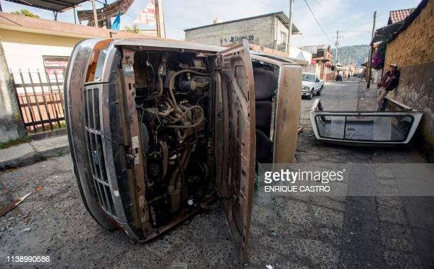 View of a car damaged during a protest after the news that the city Mayor David Otilica had been kidnapped and murdered early in the morning in...