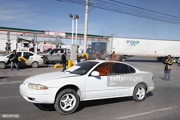 View of a car set on fire in front of a gas station after a protest against the fuel price hikes in Ciudad Juarez Chihuahua state Mexico on January...