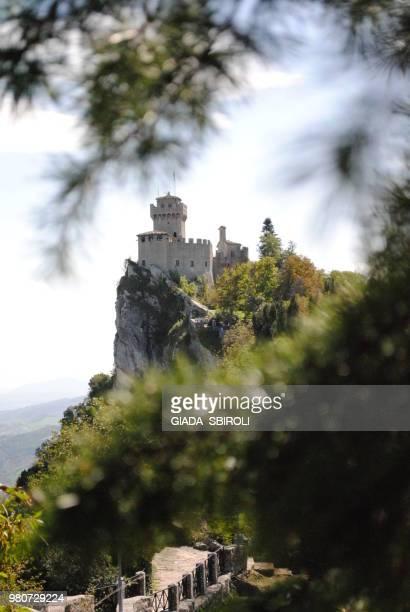 view of a castle on rock through branch, guaita, city of san marino, san marino - san marino fotografías e imágenes de stock