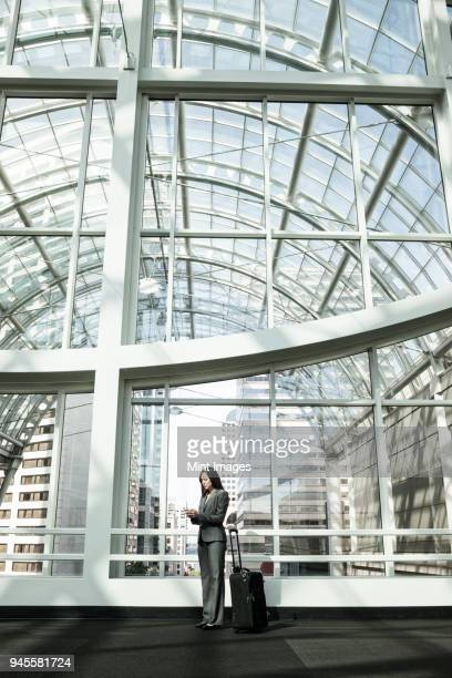 View of a Caucasian business woman in a suit coat standing in a covered glass walkway.