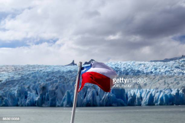 View of a Chilean flag waving near the Grey glacier at the Torres del Paine National Park in Magallanes Chile on November 29 2017 A thousandyearold...